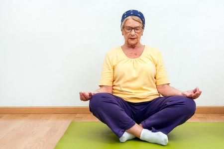 golden ager: Portrait of Elderly woman practising yoga in gym.