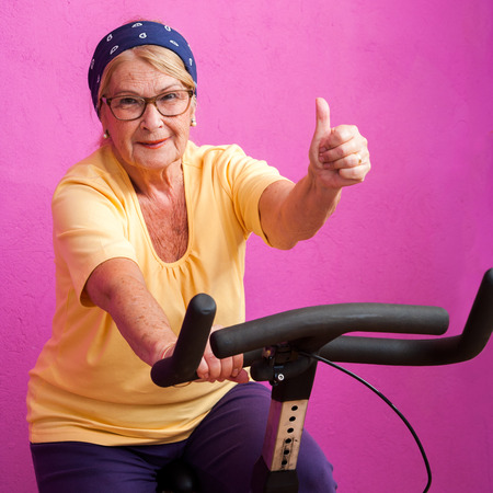 senior fitness: Fit senior woman doing thumbs up on at spinning session in gym. Stock Photo
