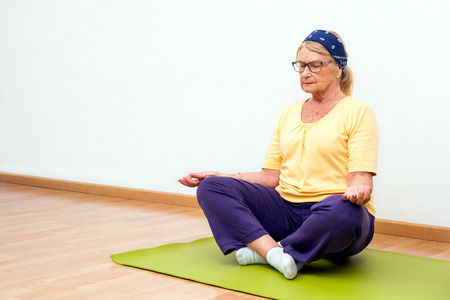 golden ager: Portrait of Senior woman meditating in gymwith eyes closed.