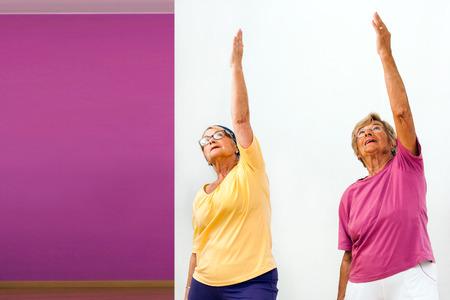 Portrait of two Senior women doing aerobics in gym.
