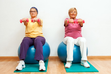Portrait of Two elderly women doing muscle exercises with weights in gym. photo