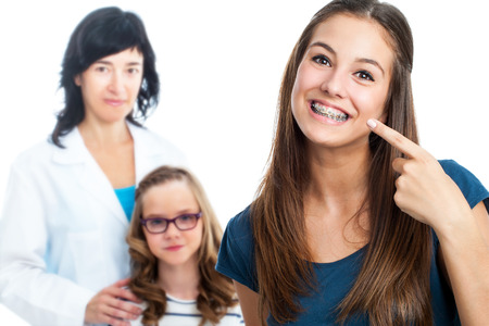 patients: Portrait of Teen girl pointing at dental braces with doctor and little girl in background.