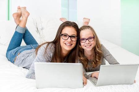 sklo: Portrét atraktivní dospívající studentských nošení brýlí se mladá sestra relaxaci s notebooky doma.