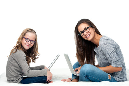 Portrait of teen student with younger sister working on laptops.Isolated on white background. photo