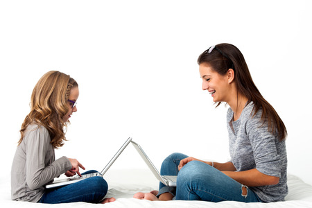 Portrait of Young Girls working together on laptops.Isolated on white background. photo