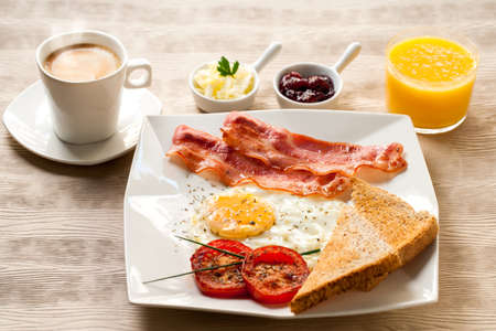 plato del buen comer: Primer plano de un desayuno continental con caf� y jugo de naranja sobre la mesa de madera.