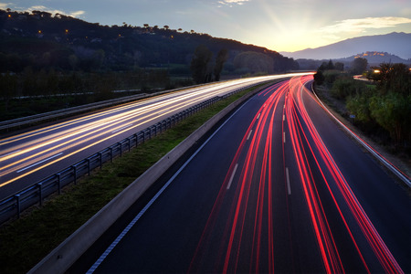 frenetic: Colorful Light beams of moving vehicles on busy highway at dusk. Stock Photo