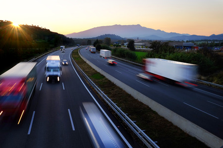 long road: Colorful Twilight scene of frenetic highway with fast moving vehicles in blurry motion. Stock Photo