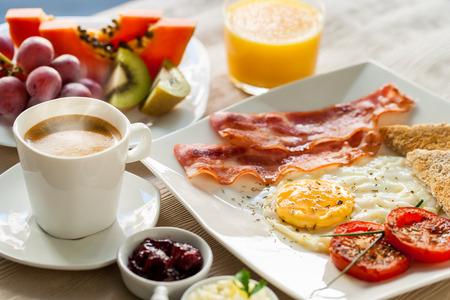 huevos fritos: Close up de desayuno continental saludable con fruta fresca y café molido.