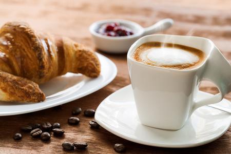 plato del buen comer: Extreme close up de caf� cremoso en mesa de madera con croissant en el fondo.