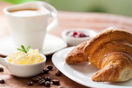 De cerca los detalles de croissant con mermelada y mantequilla y una taza de café en el fondo.