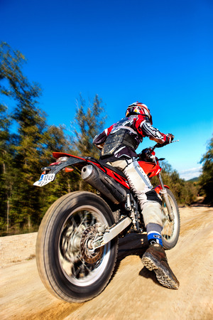 action shot: Close up action shot of Fast moving motocross rider on dirt road against blue sky. Editorial