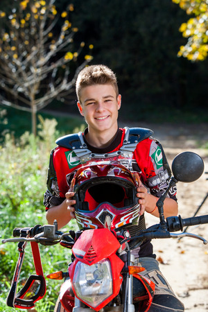 avocation: Close up outdoor portrait of handsome teen boy sitting on motocross motorcycle and wearing sport outfit.