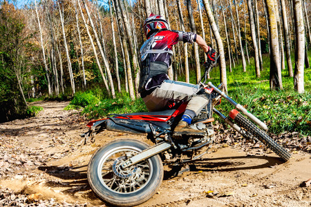 dirt road recreation: Motocross rider doing spin with wheels on dirt road in forest. Stock Photo