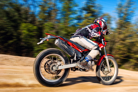 avocation: Motion shot of motocross rider on gravel road with blurry background. Stock Photo