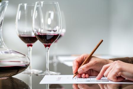 copa de vino: Extreme close up de tomar notas a mano femenina en la degustaci�n de vino tinto.