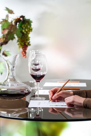 Macro vicino di scrivere note a mano femminili su carta alla degustazione di vini.