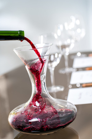 Macro close-up van rode wijn gieten in karaf bij wijnproeverij.