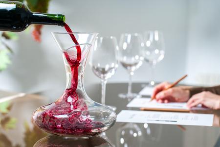 와인 시음 세션에서 디 켄 터에 레드 와인을 붓는 소믈리에의 닫습니다.