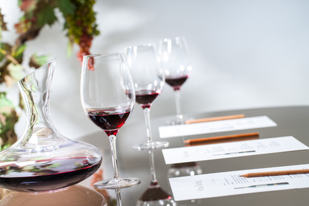 Close up of red wine decanter with glasses on table. Banque d'images