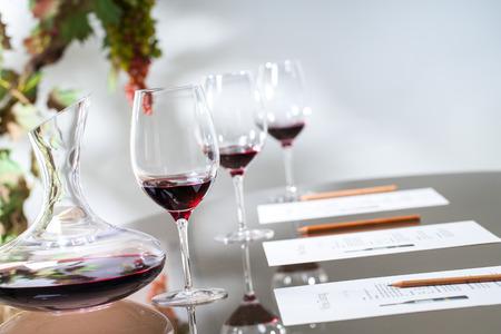 Close-up van rode wijn karaf met een bril op tafel.