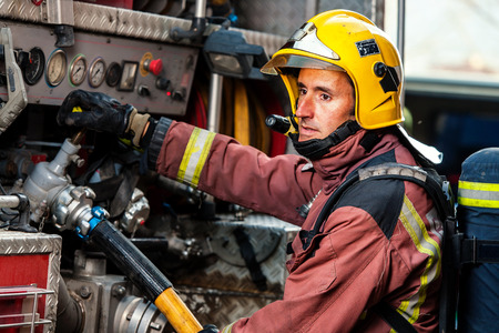 fire fighter: Fireman controlling water pressure at back of fire truck. Stock Photo