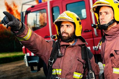 camion de bomberos: Bomberos con el camión de bomberos y enormes llamas en el fondo a punto de tomar acción.