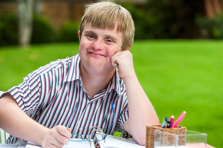 Close up portrait of young males student with down syndrome at desk holding glasses. photo