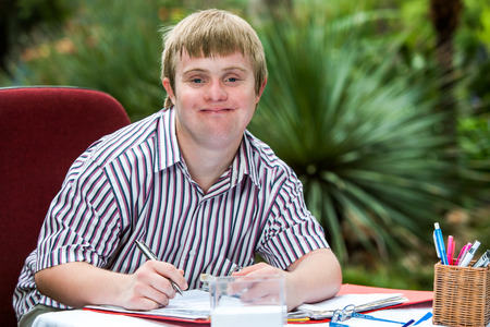 Close up portrait of young male student with down syndrome at study desk outdoors.