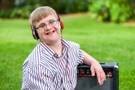challenged: Close up portrait of young man with down syndrome wearing headphones outdoors.