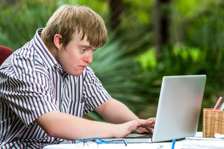 Portrait of concentrated young man with down syndrome working on laptop outdoors.