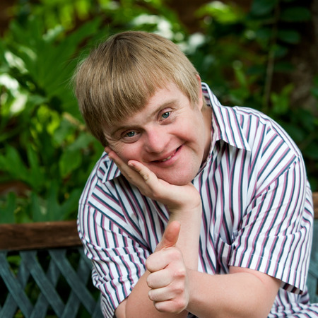 Close up portrait of cute boy with down syndrome doing thumbs up in garden.