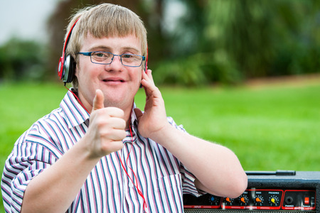 challenged: Close up portrait of down syndrome boy with headset doing thumbs up outdoors.