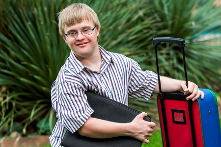 Close up portrait of young Down syndrome student with file and trolley. Banque d'images