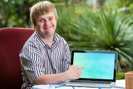Close up portrait of friendly young student with down syndrome pointing at blank laptop screen.Sitting at desk in garden.