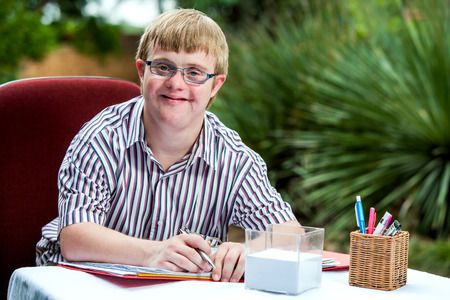 Close up portrait of handicapped student wearing glasses at desk in garden.