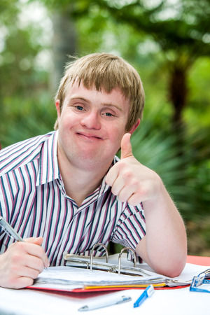 Close up portrait of handicapped student doing thumbs up at desk outdoors.