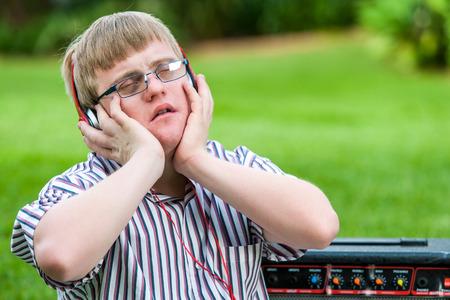 Close up portrait of handicapped boy enjoying music on head phones outdoors. photo
