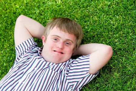 challenged: Close up portrait of handicapped boy laying with hands under head on green grass. Stock Photo