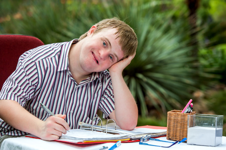 challenged: Close up portrait of Handicapped student resting on hand at desk in garden. Stock Photo