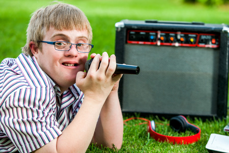 disadvantaged: Close up portrait of handicapped boy singing with microphone and amplifier outdoors. Stock Photo