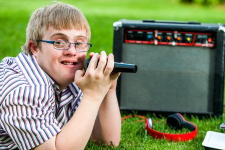 Close-up portret van gehandicapte jongen zingen met microfoon en versterker buiten. Stockfoto