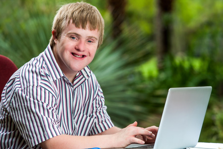 Portrait of happy handicapped young man typing on laptop in garden.