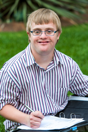 adult: Close up portrait of young handicapped student writing in file outdoors.