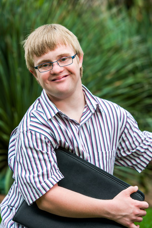 disabled: Close up portrait of young student with down syndrome holding files outdoors.