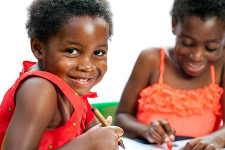 niños dibujando: Close up retrato de lindo niño africano en la mesa la celebración de crayón con el amigo en el fondo.