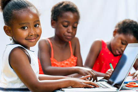 Portrait of cute little African girl doing homework on computer with friends at desk.Isolated on light background. photo
