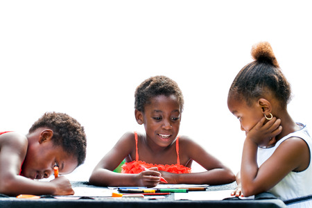 Portrait of three African kids drawing together with crayons at desk.Isolated on white background. Stock Photo