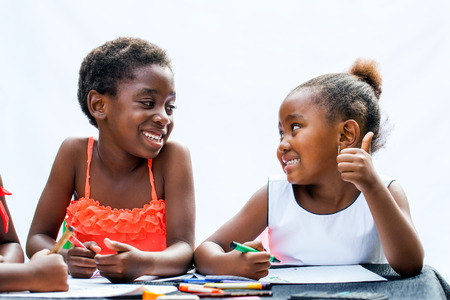 infant school: Close up portrait of two African girls with wax crayons at desk.One is showing thumbs up to friend.Isolated on light background. Stock Photo