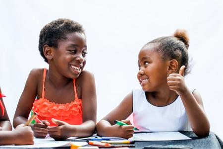 Close-up portret van twee Afrikaanse meisjes met waskrijtjes op desk.One is zien thumbs up te friend.Isolated op lichte achtergrond.